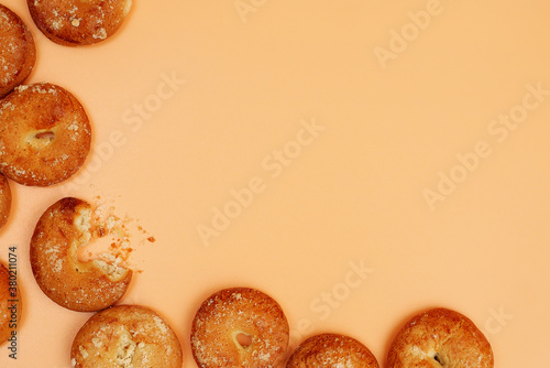 Valokuvatapetti frame composed of round shortcake brown cookies on yellow background