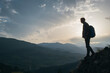 Silhouette of a backpacker standing in mountains