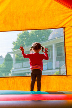 Girl Looking Out Window Of Bouncy House