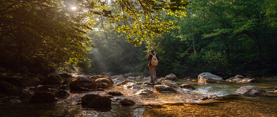 Happy male hiker trekking outdoors in forest near river
