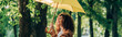 Panoramic shot of curly woman laughing while holding yellow umbrella in park