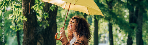 Obraz Panoramic shot of curly woman laughing while holding yellow umbrella in park - fototapety do salonu