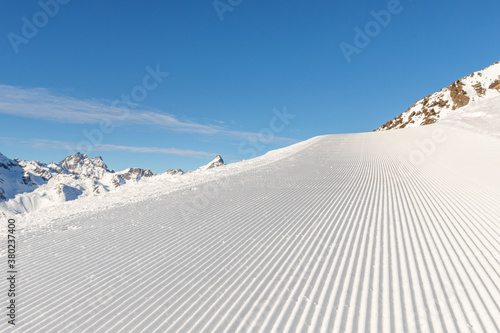 Fotografie, Obraz Close-up straight line rows of freshly prepared groomed ski slope piste with bright shining sun and clear blue sky background