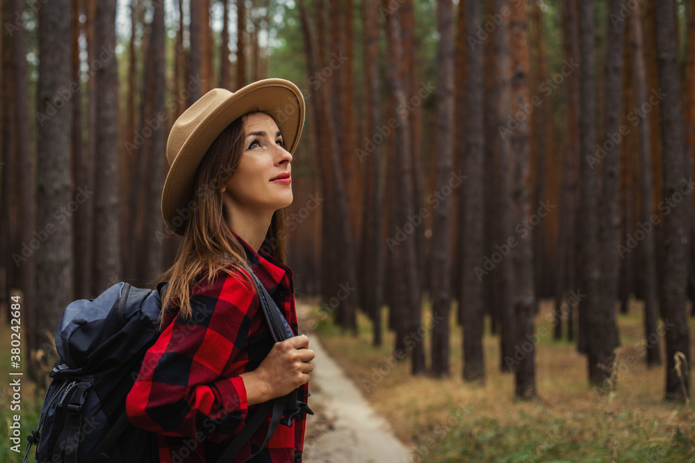 Fototapeta Young woman in a hat, red shirt and backpack looks at the treetops in a pine forest. Camping in the woods