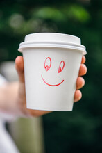 Hands Holding Paper Drinking Cup With Smiley Face Drawn On