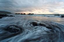 Sunrise At A Rocky Beach With Golden Sunlight Reflected On Seawater And Turbulent Waves Beating The Rocks Under Dramatic Dawning Sky At Beautiful Wai'ao Coast, Yilan ( Ilan ), Taiwan (Long Exposure)