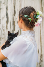 Woman In The Wedding Dress Holding A Black Cat