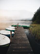Wooden Pier And Boats On The Wilderness Lake At Romania,Saint Anne,Transylvania. Wonderful Idyllic Landscape With Misty Sunrise. Saint Anne,Romania,Transylvania.