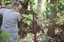Senior Woman Fetching Water From An Artesian Well At Backwoods Of Her Tree Farm