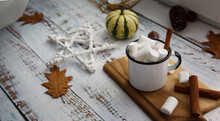 A Cup Of Cocoa With Marshmallows Stands On A Wooden Windowsill And Next To It Lies A Small Striped Pumpkin And A White Pentacle