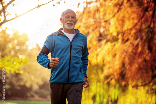 Senior man jogging outdoors. Fotobehang