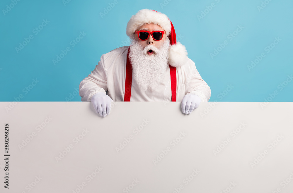 Fototapeta Portrait of his he nice attractive funky amazed stunned white-haired Santa holding in hands copy space board advert ad attention isolated over bright vivid shine vibrant blue color background
