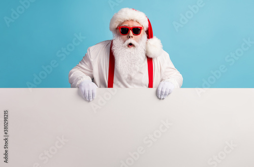 Portrait of his he nice attractive funky amazed stunned white-haired Santa holding in hands copy space board advert ad attention isolated over bright vivid shine vibrant blue color background