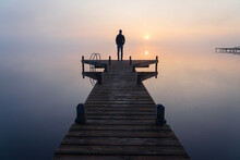 A Man Looking At The Sunrise On A Foggy, Tranquil Morning.