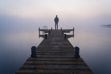 A Man Looking Over A Lake On A Foggy, Tranquil Morning.