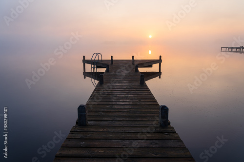 Fototapeta A jetty in a lake during a tranquil, foggy dawn.