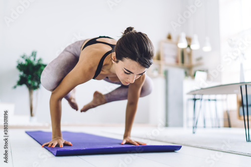 Focused woman doing yoga handstand at home