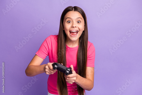 Fototapeta Photo portrait of young schoolgirl playing video games holding gamepad with both hands screaming laughing wearing pink casual t-shirt isolated on purple color background obraz