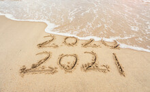 2021 And 2020 Inscription Written In The Wet Beach Sand With Sea Water Wave.
