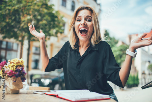 Portrait of astonished female student spread hands feeling excited with finished Canvas Print