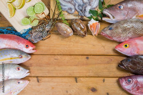 Variety of fresh tropical fishes, lobster, seashells and octopus. Ingredients from Venezuela in South America. Wooden Bacground