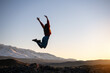 Slim girl jumps against mountains and sunset