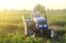 A Farmer On A Tractor Drives A...