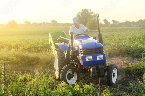 A farmer on a tractor drives across the farm field Wallpaper Mural