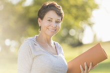 Mature Woman Holding Yoga Mat Outdoors
