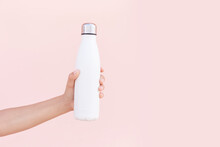 Close-up Of Female Hand Holding Reusable, Steel Eco Thermo Water Bottle Of White, Isolated On Background Of Pastel Pink Color With Copy Space. Be Plastic Free. Zero Waste. Environment Concept.