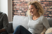 Blond Woman Laughing On Sofa