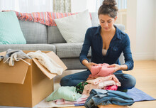 Woman Packing Clothes To Box
