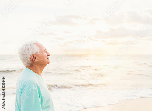 Side view of senior man smiling on beach - 380356464