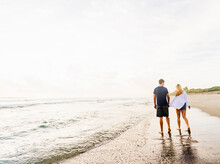 Young Couple Walking Along Surf Line Of Sandy Beach, Holding Hands