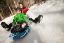 Young Woman Sledding With Boy (4-5)