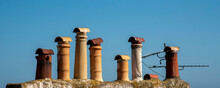 Ramsgate, Kent, England, UK. 2020.  A Line Of Old Decorative Chimney Pots Against A Blue Sky,