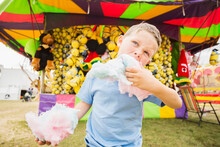 Boy (4-5) Eating Cotton Candy In Amusement Park