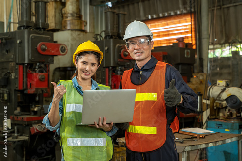 Obraz na plátne Industrial workers learning work instructions holding laptop computer at factory