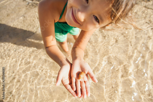 Girl (6-7) playing on beach - 380364085