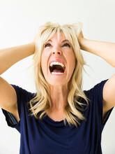 Studio Portrait Of Blonde Woman Screaming