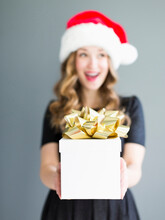 Studio Portrait Of Woman Wearing Santa Hat Holding Gift
