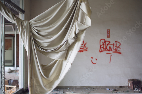 Fototapeta A torn curtain flails in the wind over a broken window at an abandoned hospital in Japan obraz