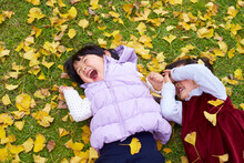 Two Lovely Asian Kids Playing In The Autumn Park