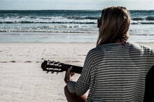 Girl Facing The Ocean, Playing Guitar