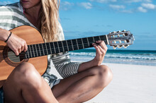Girl On Beach Playing Guitar