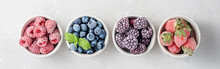 Frozen Berries In Small Bowls Against Concrete Background.Top View.