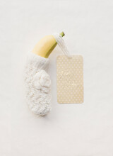 Simlicity Of A Banana In Winter Clothes Made Of Wool With A Label Happy Holidays Written On It