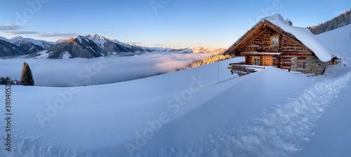 Fotografía Snow covered mountain hut old farmhouse in the Austrian alps at sunrise against blue sky