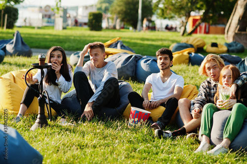 Obraz na plátně Young multi ethnic group of people watching movie at poof in open air cinema