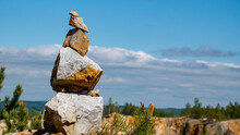 Stack Of Stones With Clouds And Blue Sky In The Background.